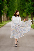 Woman wearing linen Sondeflor floral skirt and white linen shirt.