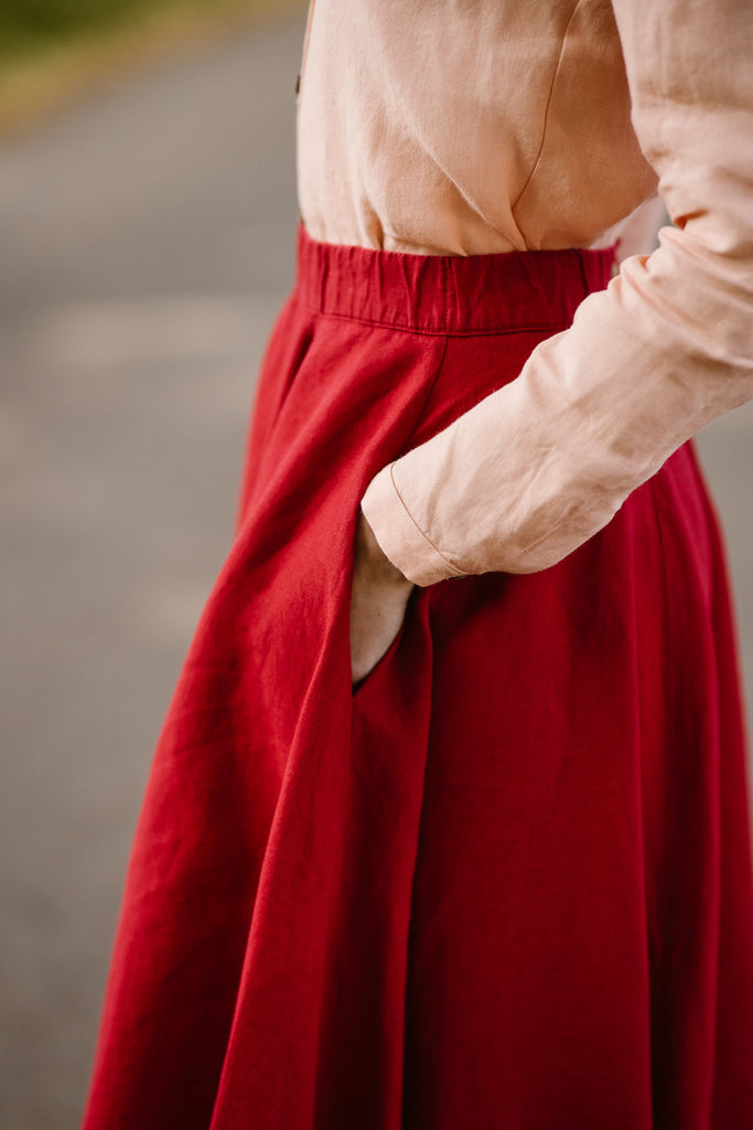 Woman wearing red color linen midi skirt, up close image of a pocket