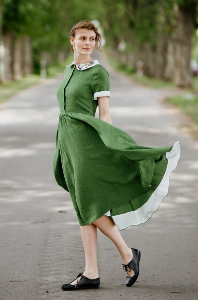 Woman wearing green classic dress with short sleeves and garden peter pan collar, picture from the side