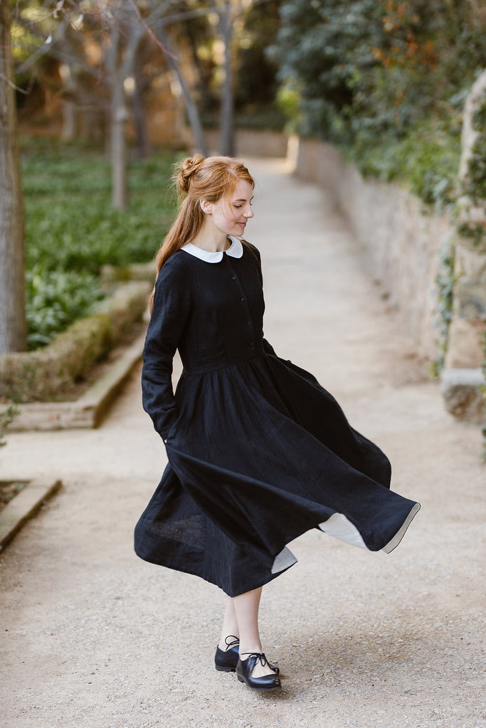 Model wearing black classic dress with long sleeves and white collar, picture from the front