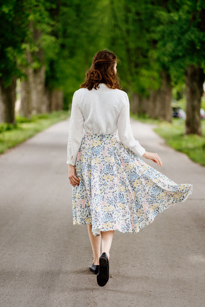 Woman wearing linen floral skirt and white linen shirt, image from the back.