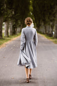 Woman wearing grey dress with long sleeves, picture from the back