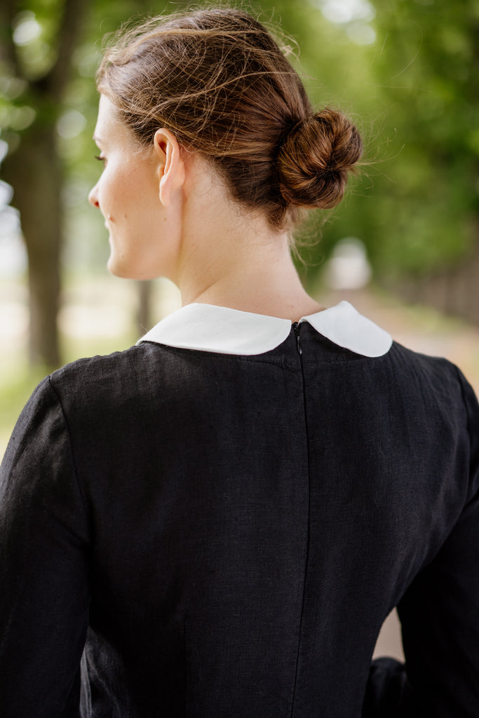 Woman in a black linen dress with white collar, pictured from the back