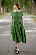 Woman wearing green classic dress with short sleeves and garden peter pan collar, picture from the front
