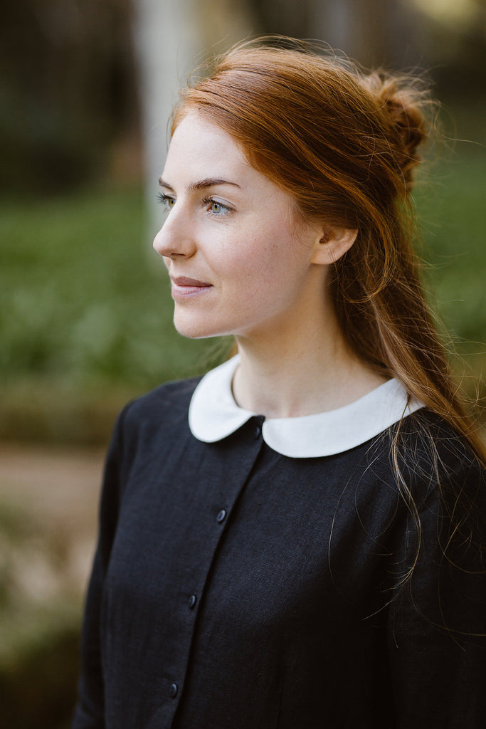 Woman wearing black classic dress with long sleeves and white collar, up close image from the front