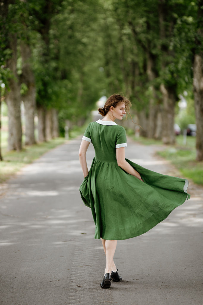 Woman wearing green classic dress with short sleeves and garden peter pan collar, image from the back