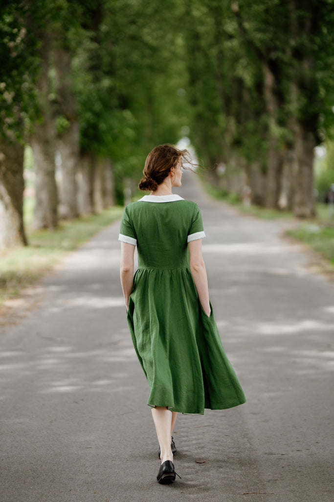 Woman wearing green classic dress with short sleeves and garden peter pan collar, picture from the back