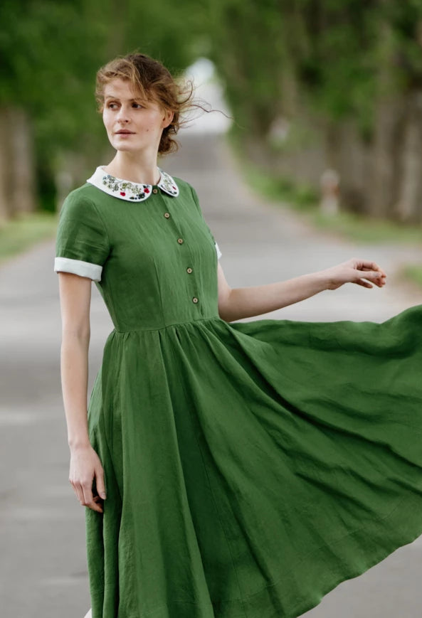 Model wearing green classic dress with short sleeves and garden peter pan collar, image from the front