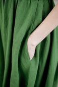 Woman wearing green classic dress with short sleeves and garden peter pan collar, up close image of a pocket