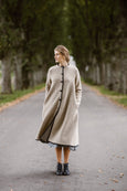 Woman wearing beige color long wool coat, image from the front