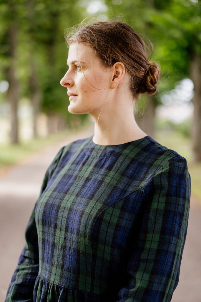 Woman in a blue tartan linen dress, up close image from the front