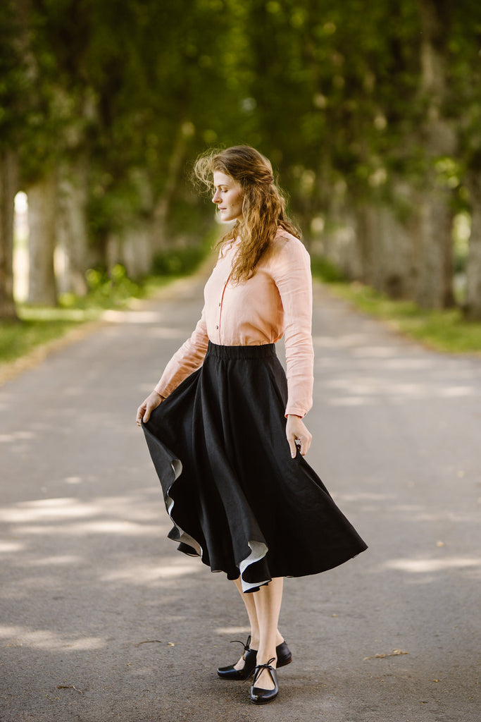 Woman wearing black linen midi skirt, image from the side