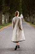 Woman wearing beige color long wool coat, image from the back