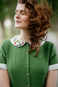 Woman wearing green classic dress with short sleeves and garden peter pan collar, up close image from the front