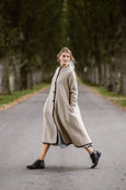 Woman wearing beige color long wool coat, image from the side