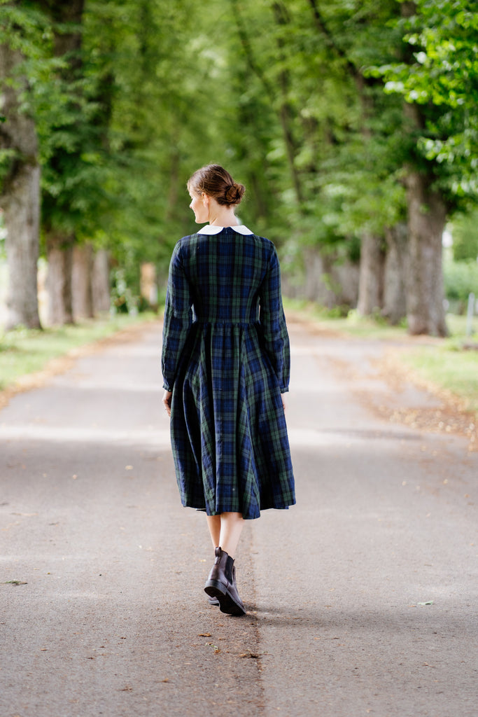 Model pictured from the back in a blue tartan midi dress