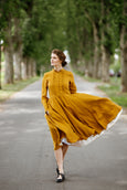 Woman wearing yellow dress with long sleeves, picture from the front.