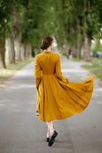 Model wearing yellow dress with long sleeves, image from the back.