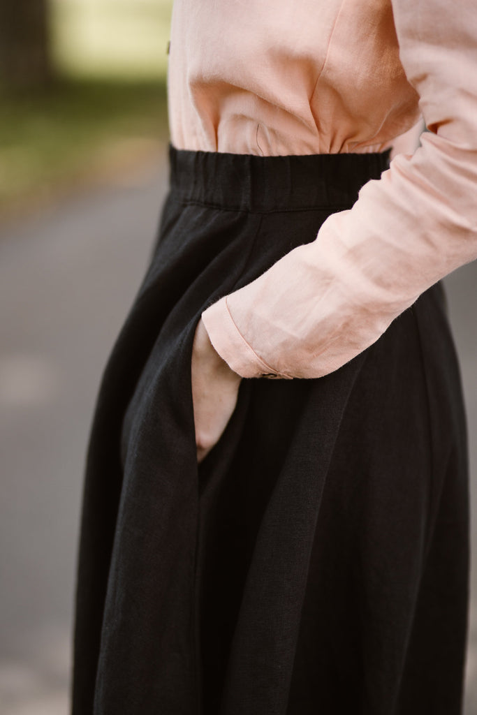 Woman wearing black linen midi skirt, up close image of a pocket
