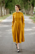 Woman wearing yellow dress with long sleeves, image from the front.