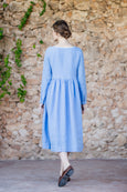 Woman walking towards wall wearing light blue linen dress with loose waist and long sleeves