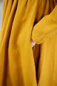 Woman wearing yellow dress with long sleeves, up-close image of a pocket.