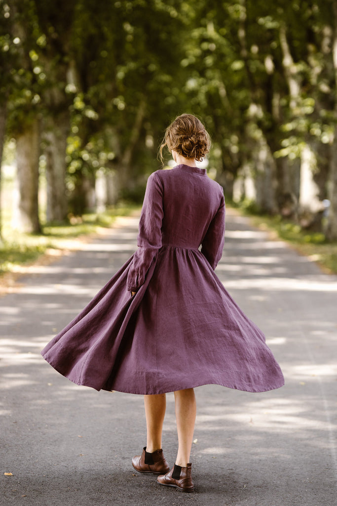 Woman wearing violet color dress with long sleeves, image from the back
