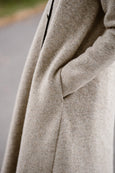 Woman wearing beige color long wool coat, up close image of a pocket