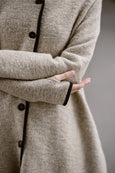 Woman wearing beige color long wool coat, up close image from the front