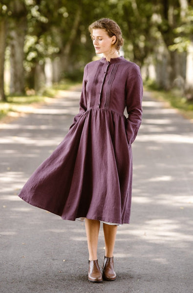 Woman wearing violet color dress with long sleeves, picture from the front
