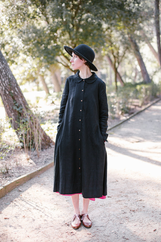 Woman wearing black button down dress with long sleeves, picture from the front.
