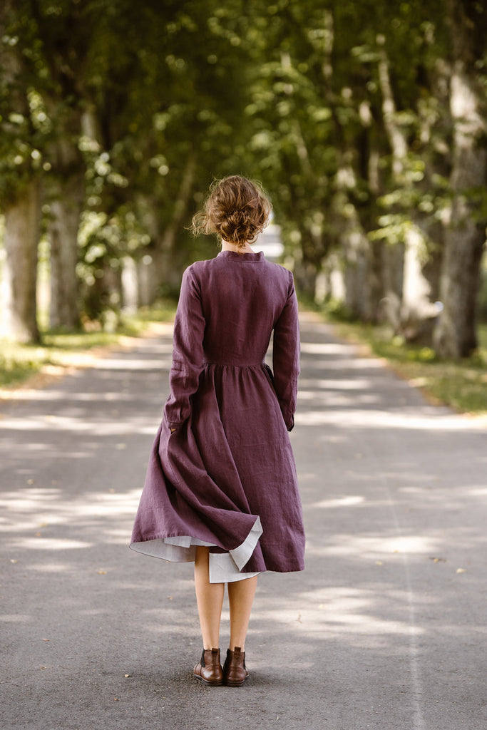 Woman wearing violet color dress with long sleeves, picture from the back