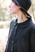 Woman wearing black button down dress with long sleeves, up close image from the front.