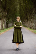 Woman wearing green color long wool sweater, image from the front