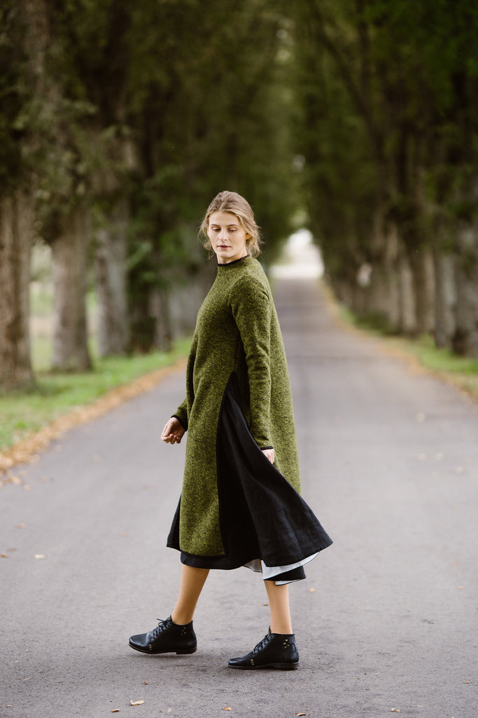 Woman wearing green color long wool sweater, image from the side