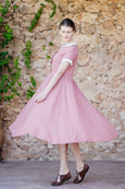 Woman in pastel pink linen dress and full A-line skirt and short sleeves