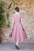 Picture form the back: woman in pink linen dress walks towards the stone wall