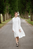Woman wearing white button down dress with long sleeves, picture from the front.