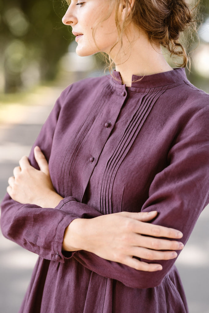 Woman wearing violet color dress with long sleeves, up close image from the front