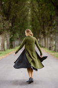 Woman wearing green color long wool sweater, image from the back