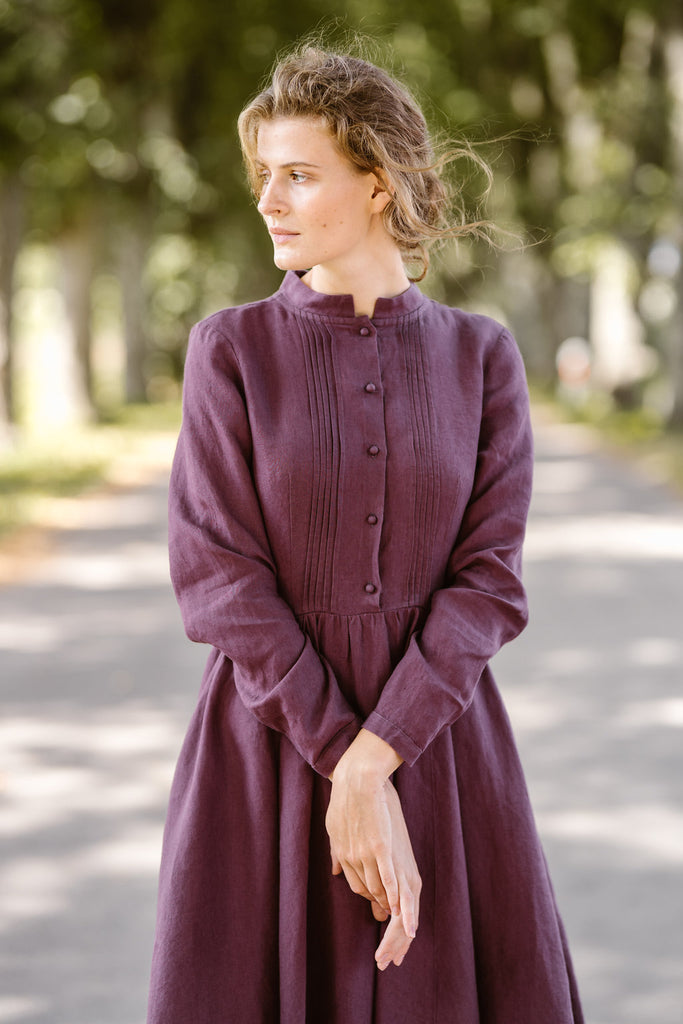 Model wearing violet color dress with long sleeves, image from the front