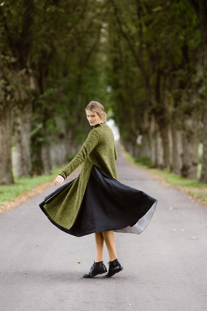 Woman wearing green color long wool sweater, picture from the side