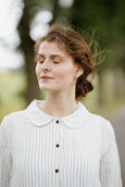 Woman wearing white button down dress with long sleeves, up close picture from the front.