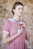 Pastel pink linen dress with embroidered collar and white rolled up sleeves
