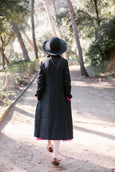 Woman wearing black button down dress with long sleeves, picture from the back.
