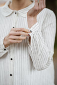 Woman wearing white button down dress with long sleeves, up close image from the front.