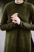 Woman wearing green color long wool sweater, up close image from the front