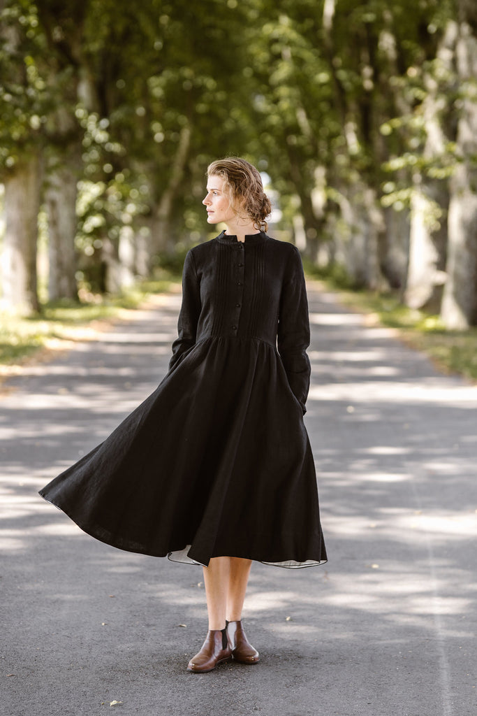 Woman wearing black dress with long sleeves, picture from the front.