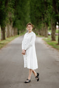Woman wearing white button down dress with long sleeves, picture from the side.