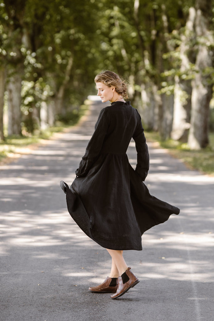 Woman wearing black dress with long sleeves, image from the side.